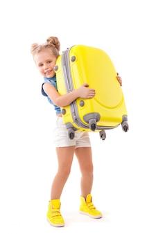 Attructiva niña linda con camisa azul, pantalones cortos blancos y gafas de sol con maleta amarilla