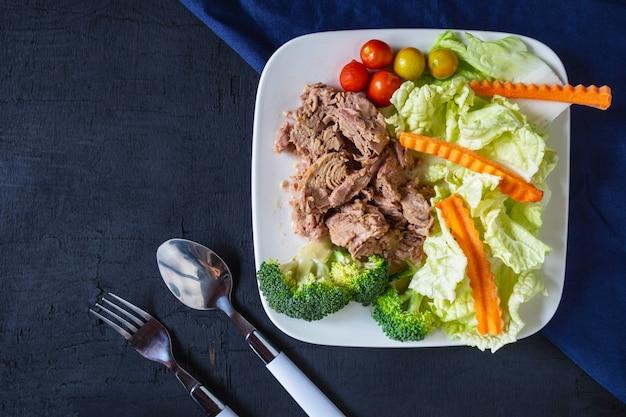 Atún y verduras saludables en un plato sobre la mesa.