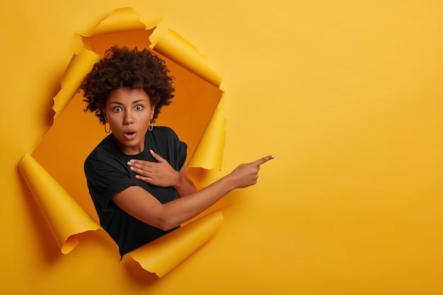 Aturdida mujer afroamericana mira con expresión asustada y sin palabras
