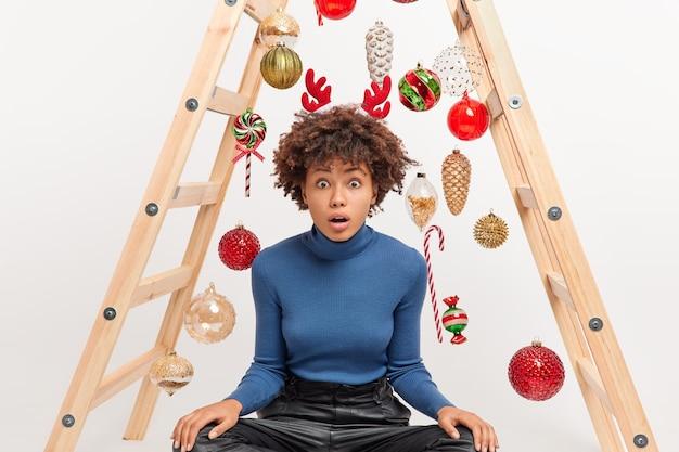Aturdida mujer de piel oscura se sienta con las piernas cruzadas sobre la escalera con juguetes de navidad se prepara para la celebración de las vacaciones de invierno lleva un aro de ciervo en la cabeza con cuello alto informal. decoración navideña. que gran sorpresa