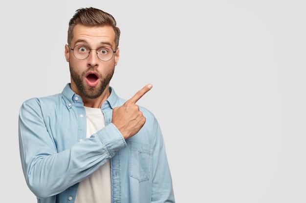 Aturdido apuesto hombre sin afeitar con expresión facial de sorpresa, vestido con una camisa de moda, apunta en la esquina superior derecha