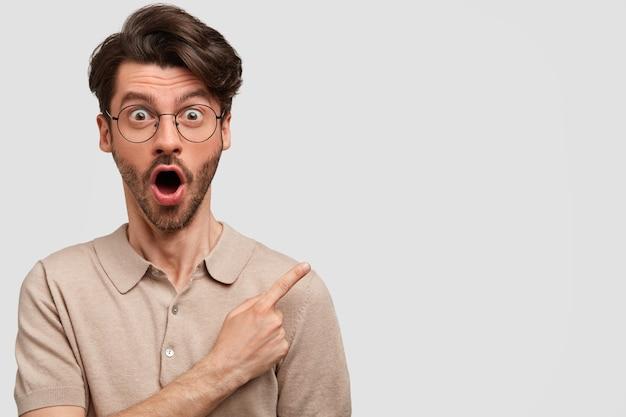 Aturdido apuesto joven con cabello oscuro, tiene expresión de sorpresa, indica con el dedo índice