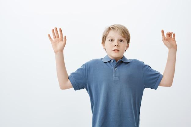 Aturdido, asustado, lindo chico con cabeza rubia, levantando las palmas de las manos en señal de rendición, conteniendo la respiración y mirando asustado, siendo atrapado cerca del refrigerador por la noche
