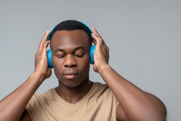 Audición, actitud. hombre de piel oscura grave concentrado con auriculares inalámbricos con los ojos cerrados escuchando atento