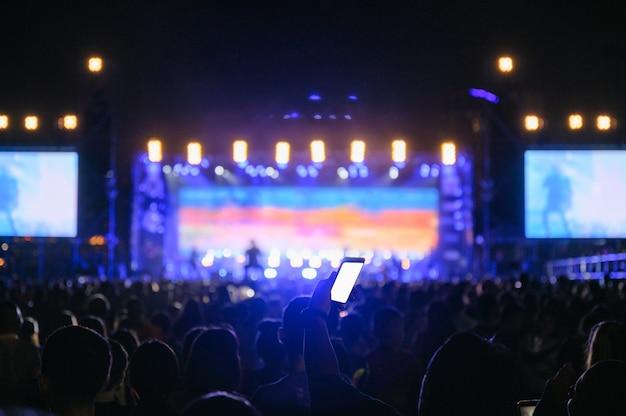 La audiencia juvenil silueta está viendo el concierto nocturno
