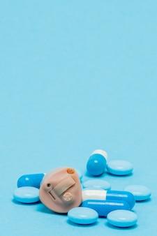 Audífono y pastillas azules