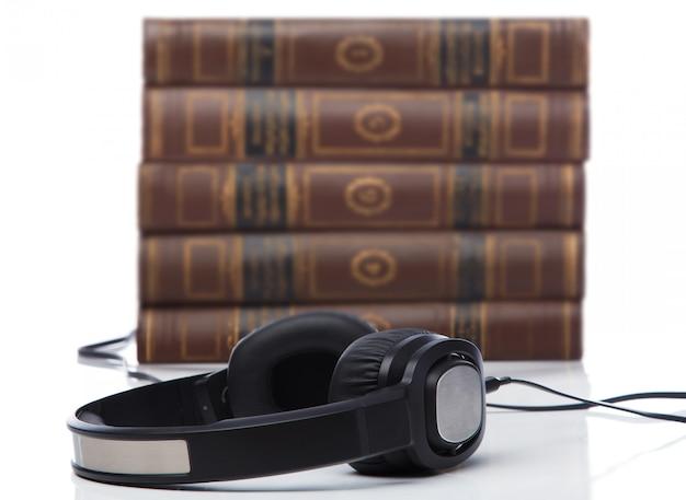 Audiolibros, auriculares en pila de libros