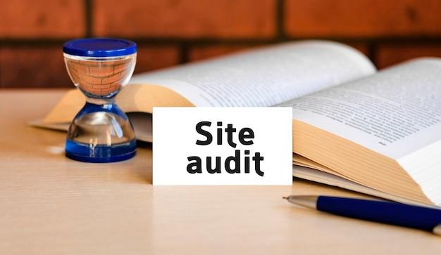 Auditoría del sitio: texto del concepto de negocio sobre un fondo blanco con un reloj de arena y un libro abierto