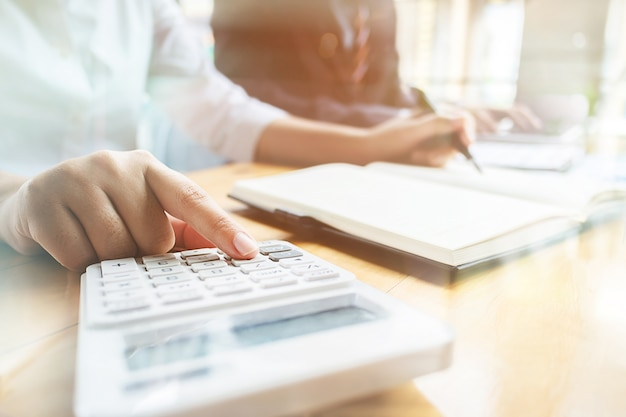 Auditorías de negocios utilizando una calculadora de datos financieros de fondo de inversión en un lugar de trabajo, concepto de riqueza