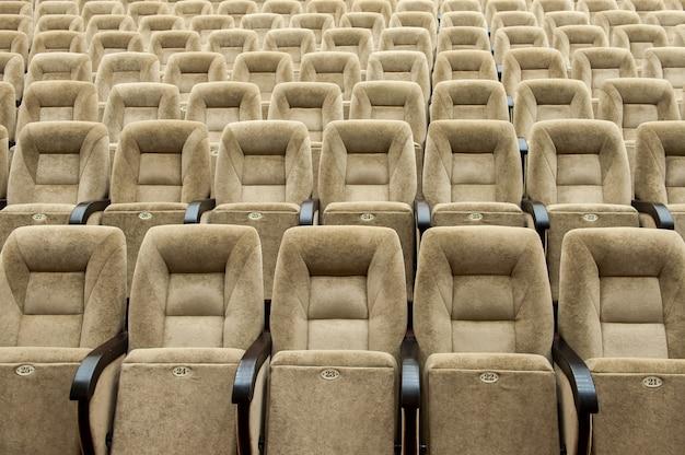 Auditorio vacío con sillas de color beige, teatro o sala de conferencias.