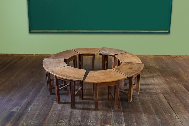 Aula antigua en la escuela con círculo fila de escritorios vacíos