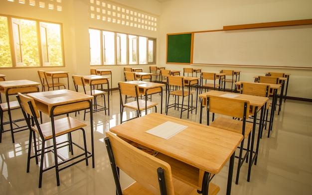Aula de la escuela con papel de examen de prueba en escritorios silla de madera