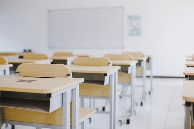 Aula vacía sin estudiantes con escritorios, sillas y pizarra durante la pandemia