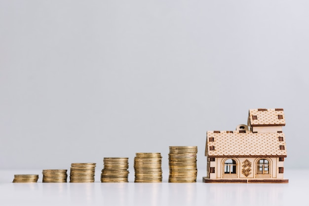 Aumentando las monedas apiladas cerca del modelo de la casa