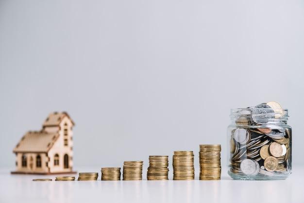Aumentando las monedas apiladas y el frasco de vidrio frente al modelo de la casa