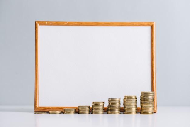Aumentando las monedas apiladas en frente de la pizarra en blanco