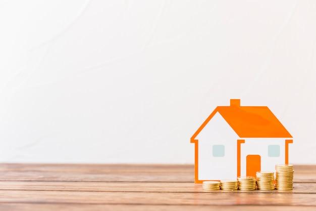 Aumentando las monedas apiladas y el modelo de la casa frente a la pared