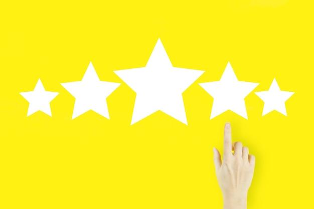Aumentar la evaluación de calificación y el concepto de clasificación dedo de la mano de la mujer joven apuntando con holograma cinco estrellas sobre fondo amarillo.