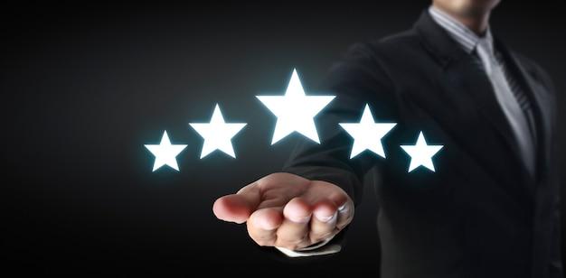 Aumente el aumento de cinco estrellas en la mano humana, aumente la evaluación de calificación y el concepto de clasificación