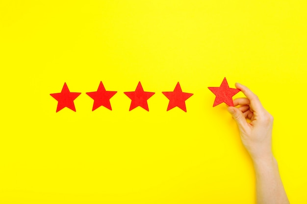 Aumento de 5 estrellas, concepto de experiencia del cliente. la mano del cliente muestra un símbolo de 5 estrellas para aumentar la calificación del servicio. excelente calificación de cinco estrellas rojas sobre fondo amarillo. concepto de satisfacción