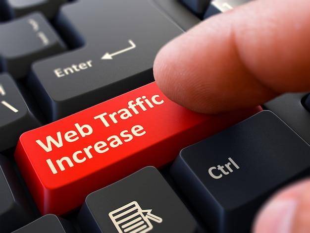 Aumento del tráfico web: escrito en la tecla roja del teclado. mano masculina presiona el botón en el teclado de la pc negro. vista de cerca. fondo borroso. render 3d.