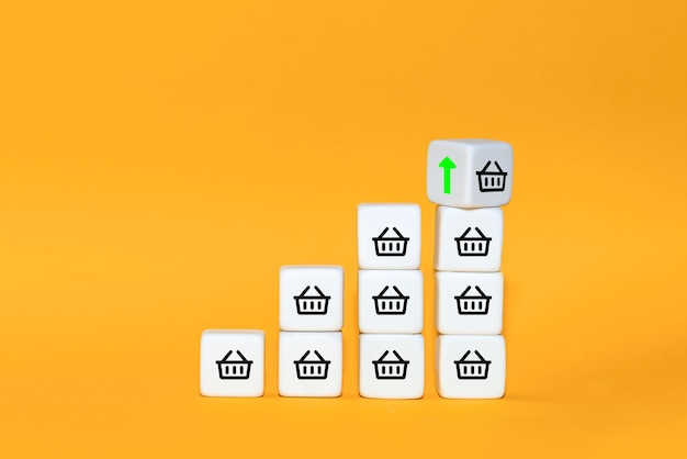El aumento del volumen de ventas hace crecer el negocio. el cubo se da vuelta con la flecha y el símbolo del carrito de compras. concepto de negocio.