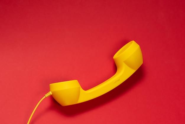 Auricular amarillo sobre fondo rojo. copie el espacio.