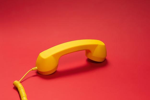 Auricular amarillo sobre superficie roja. copie el espacio.