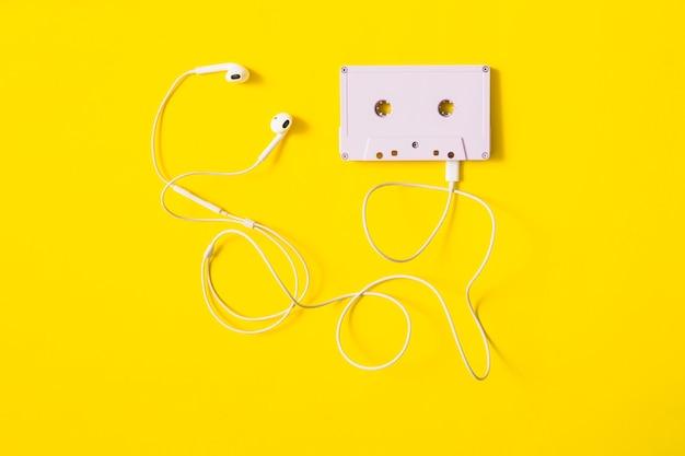 Auricular blanco conectado a cinta de cassette sobre fondo amarillo