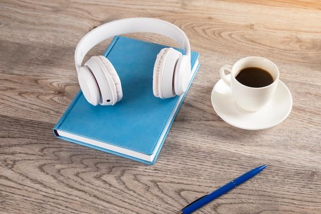Auricular en libro con café en la mesa de madera