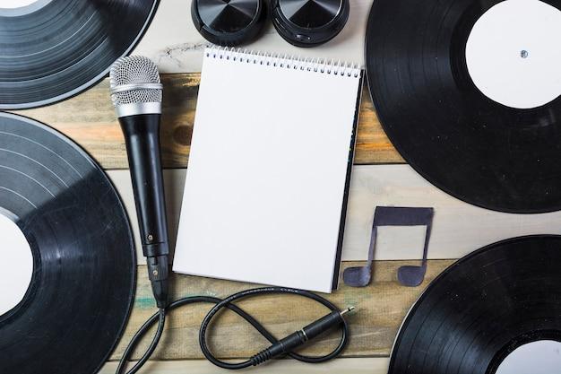 Auricular; micrófono; disco de vinilo y cuaderno de espiral en blanco con nota musical en mesa de madera.