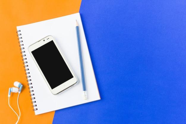 Auricular, teléfono inteligente y portátil en la vista superior sobre fondo azul y naranja