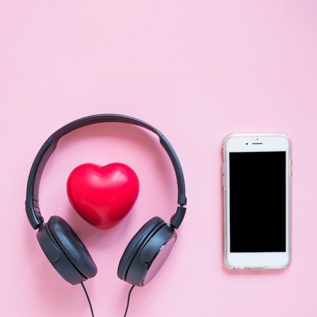 Auriculares alrededor de la forma de corazón rojo y teléfono inteligente contra el fondo rosa