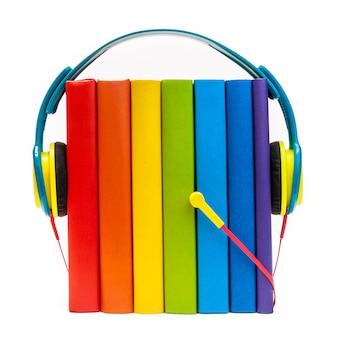 Auriculares alrededor de libros multicolores arco iris aislados en un concepto de audiolibros blanco