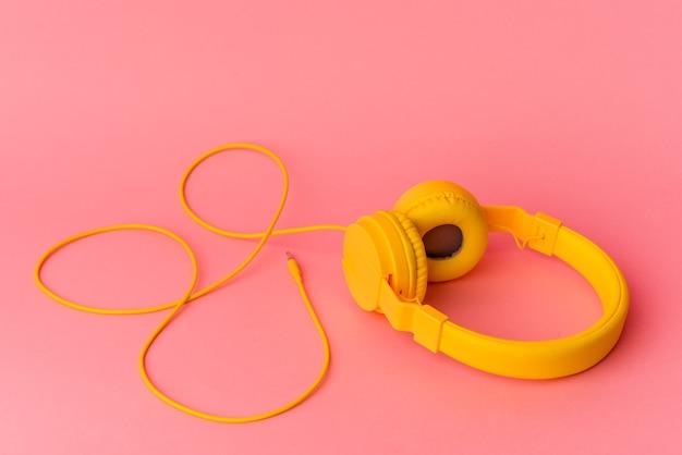 Auriculares amarillos aislados sobre fondo rosa