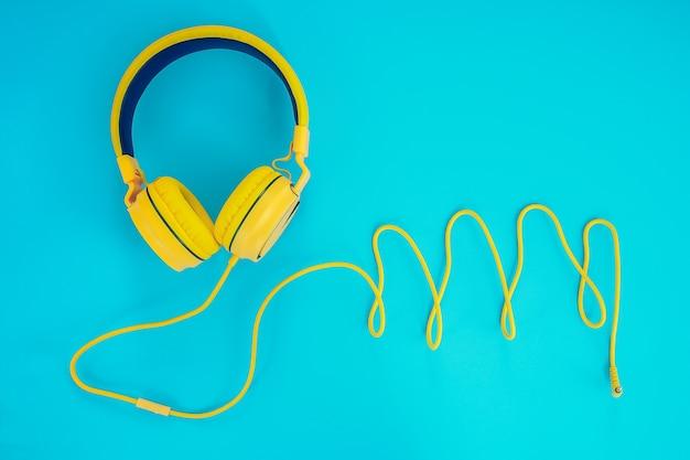 Auriculares amarillos o auriculares ordenador sobre un fondo azul pastel