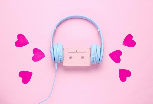 Auriculares azules con cassette de audio y corazones sobre fondo rosa