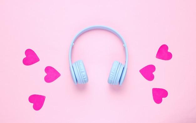 Auriculares azules y corazones sobre fondo rosa