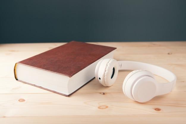 Auriculares blancos blancos en el libro y una lupa