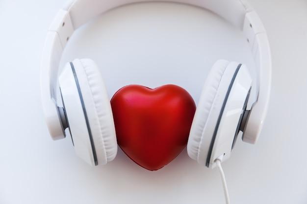 Auriculares blancos y forma de corazón rojo en el medio