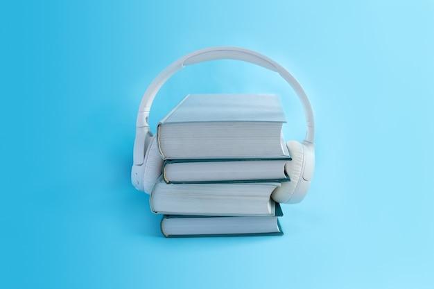 Auriculares blancos inalámbricos en una pila de libros en