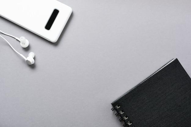 Auriculares blancos modernos, un bloc de notas para notas y un teléfono móvil en un gris