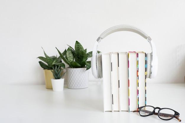 Auriculares blancos en una pila de 5 libros, vasos y flores de interior sobre la mesa con el telón de fondo de una pared blanca. concepto de audiolibro. copie el espacio.