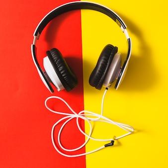 Auriculares blancos sobre el doble fondo rojo y amarillo