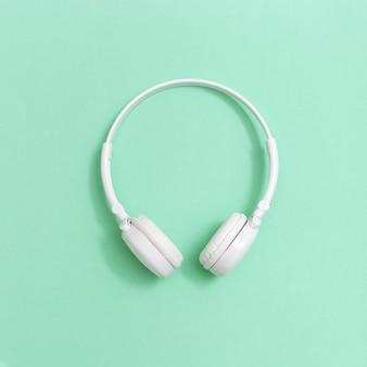 Auriculares blancos sobre papel. concepto para festivales de música, estaciones de radio, amantes de la música. estilo minimalista. tarjeta de felicitación.