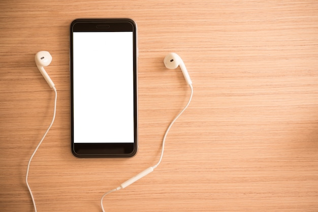 Auriculares blancos y teléfono inteligente sobre fondo de madera con espacio de copia