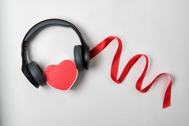 Auriculares y caja de corazón con cinta roja. concepto de amor escuchando música. fondo blanco, directamente arriba.