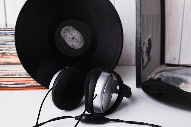 Auriculares cerca del disco de vinilo con huella digital