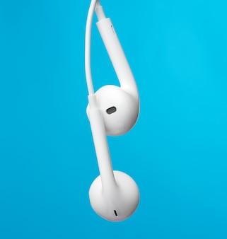 Auriculares colgantes en un cable blanco, gadget moderno en una superficie azul