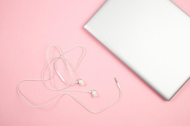 Auriculares y computadora portátil atados con alambre blancos en fondo aislado rosa. vista superior. aplanada bosquejo